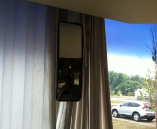 I end up turning the rearview mirror on end so the curtains fit behind it.